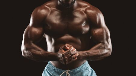 Well fit muscular man body over black studio background, cropped Stock Photo