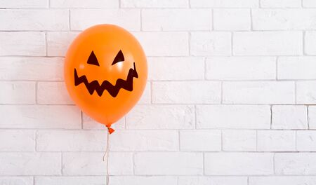 Conceptual Halloween balloon for party with scary smile on white background, panorama, copy space
