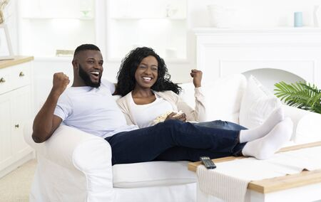 Black Millennial Couple Watching Sports On Television And Cheering, Copy Space