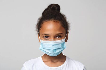 concetto di infezione. Ritratto di piccola ragazza afroamericana che indossa maschera medica, sfondo grigio