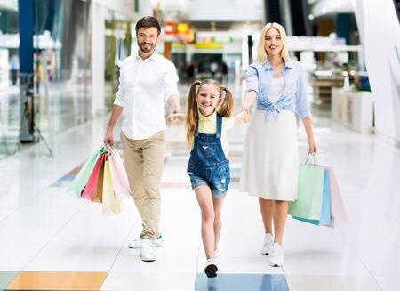 Familie lopen samen in winkelcentrum hand in hand en glimlachen naar de camera. Seizoensverkoop Stockfoto