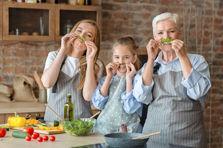 Funny female family spending good time together while cooking, making salad mustaches, kitchen interior, copy space