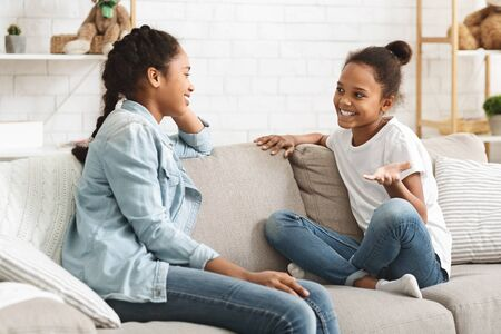 Two lovely african sisters having conversation at home, sitting on sofa at living room, copy space