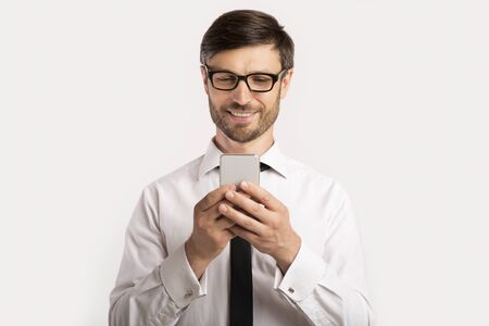 Positive Businessman Texting On Mobile Phone Standing Over White Background. Studio Shot, Free Space