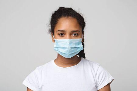 Concepto de gripe. Adolescente africana con mascarilla protectora, fondo de estudio gris