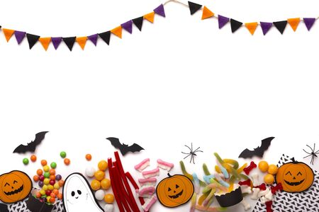 Trick or treat. Happy Halloween candies with paper decorations and copy space for greetings on white background