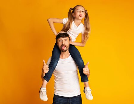 Funny Father Carrying Daughter On Shoulders Gesturing Thumbs-Up And Showing Tongues Standing On Yellow Background.