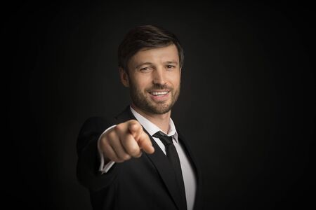 Youre Next. Confident Businessman Pointing Finger Smiling At Camera Over Black Background. Studio Shot, Free Space