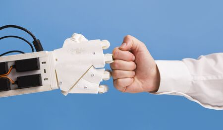 Robot and human hand making fist bump gesture on blue background
