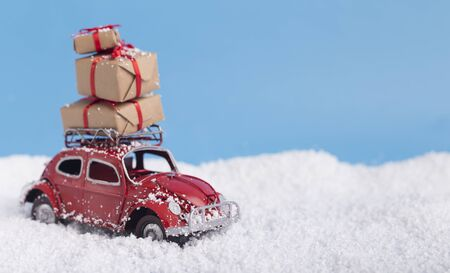 Santa Claus delivery. Red toy car with Christmas presents on background with snow