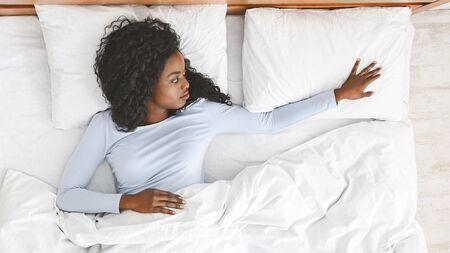 Vermisse dich. Einsamkeit-Konzept. Junges afrikanisches trauriges Mädchen, das leeres Kissen berührt, morgens im Bett liegt, Draufsicht, Panorama mit Kopienraum Standard-Bild