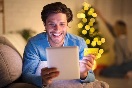 Hombre guapo de compras online en tableta en la víspera de año nuevo, mujer decorando el árbol de Navidad en el fondo