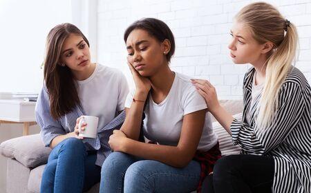 Las adolescentes consolando a su amigo molesto, discutiendo problemas y chismeando en casa