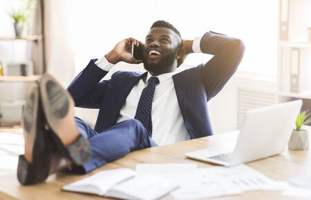 Cheerful african manager talking by phone while having break at office, leaning back on chair and putting legs on table, panorama with copy space