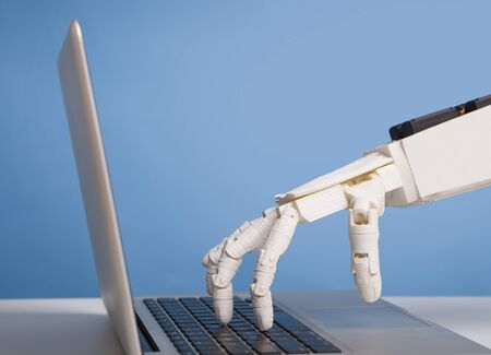 Internet bots concept. Robotic hand typing on laptop keyboard, free space
