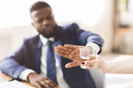 African american businessman saying no to glass of whiskey offered by female colleague, selective focus, copy space Banque d'images