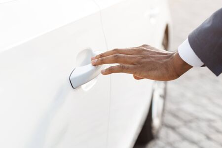 Opening his new car. Black male hand touching car handle, luxury white auto