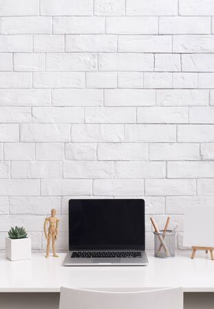 Office desk table with supplies. Laptop with blank screen in front of bricks wall in stylish office, vertical panorama