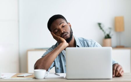Exhausted African American worker felt asleep at workplace, panorama with copy space