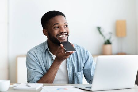 AI Technology Concept. Joyful black self-employed guy using voice assistant on smartphone managing his schedule. Copy space