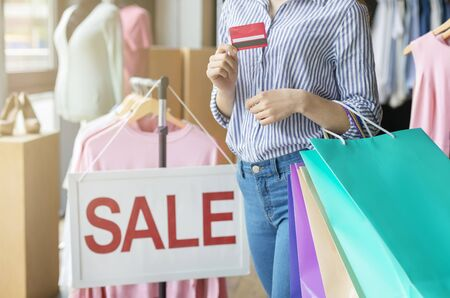 Female Hands Holding Shopping Bags And Credit Card In Front Of Saling Board, easy shopping concept Stock Photo