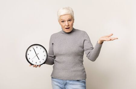 Punctuality and time management concept. Shocked elderly woman holding wall clock and gesturing with hand, copy space