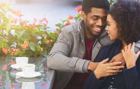Happy time together. Beautiful african american couple bonding at cafe, copy space Imagens