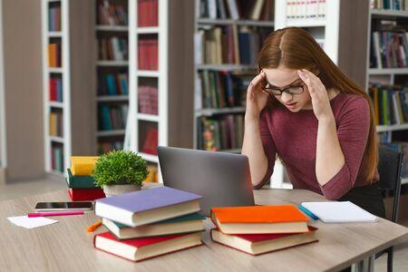 Fille caucasienne fatiguée coincée devant un ordinateur portable, se touchant la tête avec les mains, espace de copie