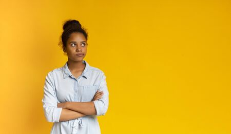 Pensive african girl thinking about something, standing with folded arms and looking up at free space. Yellow studio background