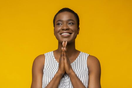 I have a hope. Cheerful afro girl looking aside, placing hands in praying gesture, yellow background