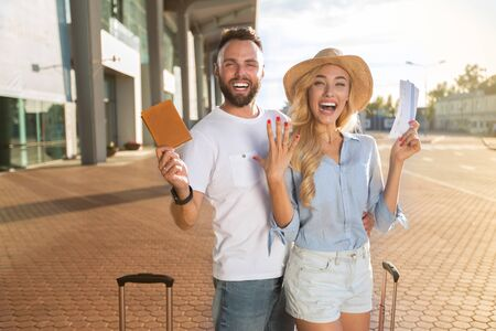 Happy newlyweds going on honeymoon and holding tickets near airport entrance, free space Reklamní fotografie
