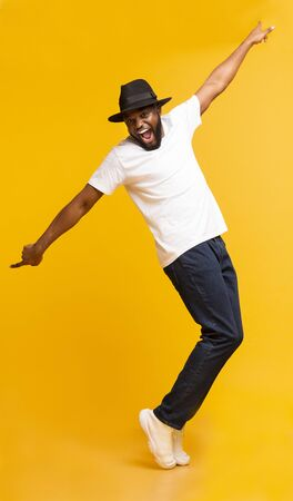 Funny Black Guy in Hat Fooling, Standing on Tiptoes Over Yellow Studio Background