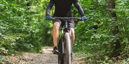 Sport equipment and clothes. Male cyclist riding bike among trees, free space
