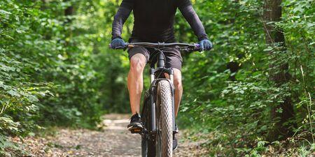 Sportausrüstung und Kleidung. Männlicher Radfahrer, der Fahrrad zwischen Bäumen reitet, freier Raum