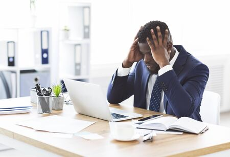 Stressed and overworked african-american young businessman sitting in office with hand on forehead, copy space Stock Photo