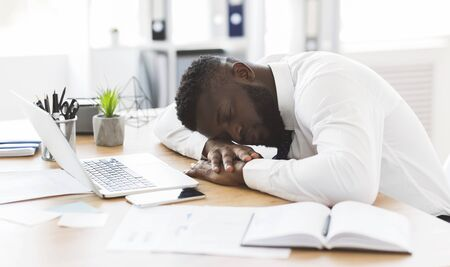 Exhausted african american young employee sleeping in his office, stress and tiredness concept, panorama with copy space
