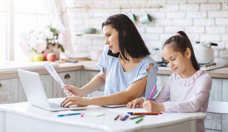 Familia ocupada. Madre trabajando desde casa mientras su hija hace sus deberes en la cocina, panorama