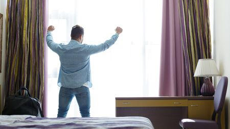 Man stretching in front of window in hotel room, panorama with copy space Archivio Fotografico - 131083572