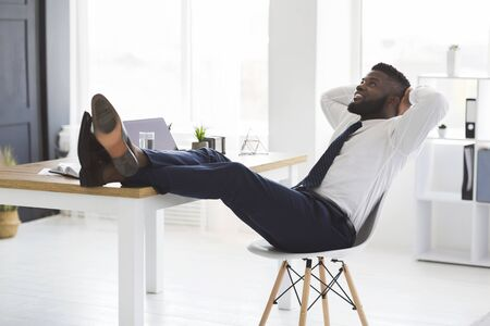 Joyful young african manager relaxing on chair in white modern office, putting legs on table, looking up, copy space