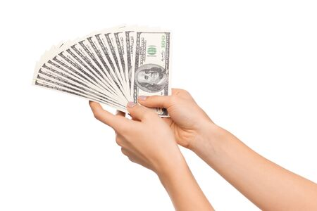 Successful investment. Fan of dollar banknotes in female hands isolated on white background