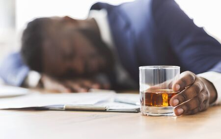 Alcoholism, drinking concept. Drunk african employee sleeping at working place, holding glass with alcohol, selective focus, panorama Stockfoto