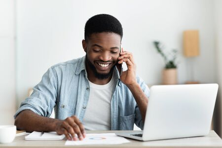Cheerful african businessman checking financial reports and talking on phone, happy about results of his company. Copy space