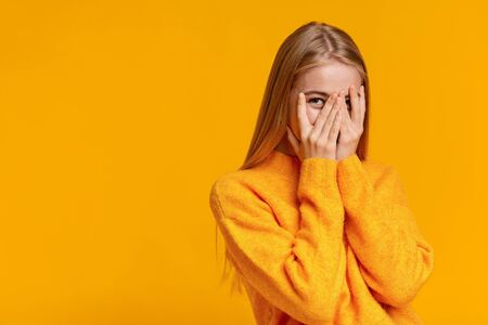 Shy teenage girl peeking through fingers, covering face with both hands over orange studio background with copy space