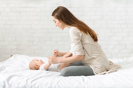 Giovane madre che gioca con il suo neonato a letto, godendosi il congedo di maternità. Copia spazio Archivio Fotografico