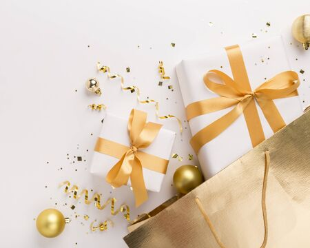 Happy holidays. Christmas presents in gold bag with confetti on white background, copy space Stock Photo