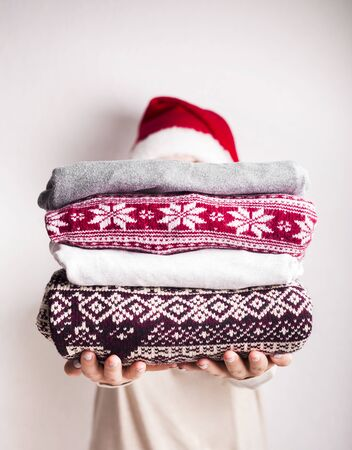 Holiday presents. Woman holding warm sweaters with Christmas pattern