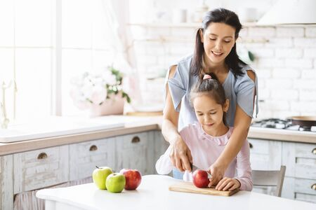 Vegetarian mother teaching her little daughter how to make fruit salad, cutting apples together