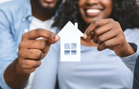 Real estate, housing and family concept. Close up of black couple holding wooden house