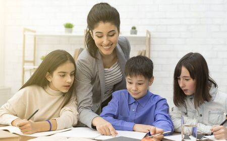 Young teacher helping children doing homework or math problem in classroom Banque d'images