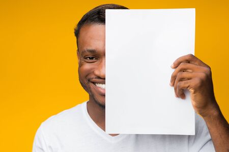 Smiling African American Man Holding Blank Paper Sheet Covering Half Of His Face Standing Over Yellow Background. Mockup Imagens